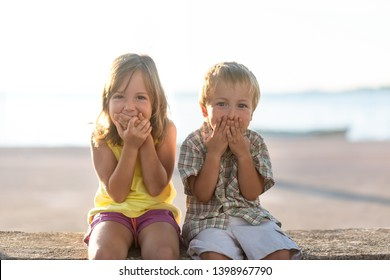 Adorable children laugh covering mouth with hands
