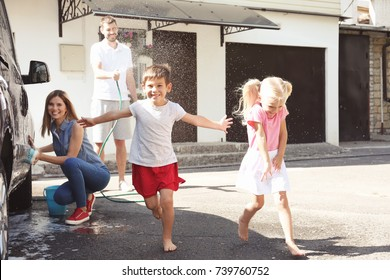 Adorable children playing while parents washing car outdoors