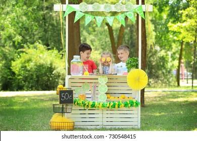 Adorable children selling homemade lemonade at stand in park