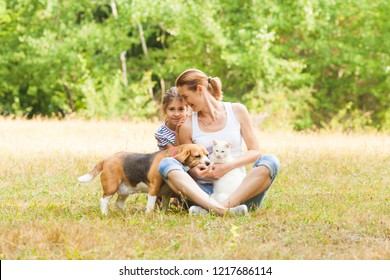 Adorable couple daughter and mom sitting on a grass with their pets