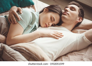 Adorable couple lying in bed and napping together embracing in a morning