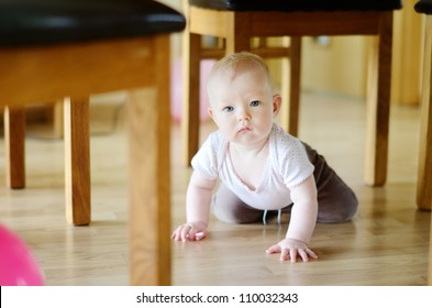Adorable crawling baby girl under a table