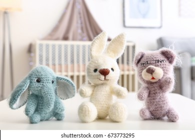 Adorable crochet baby toys on table in bedroom