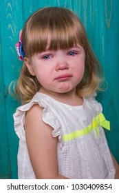 adorable crying emotionl baby in white dress on blue wooden background