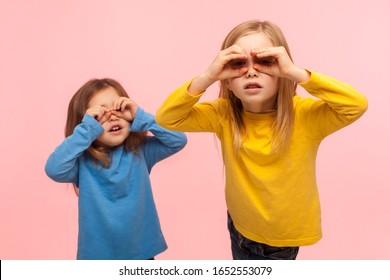 Adorable, curious, nosy two little girls looking through fingers imitating binoculars, exploring world, discovering something new with interested gaze. indoor studio shot isolated on pink background
