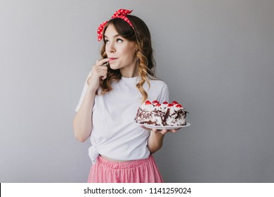 Adorable curly girl tasting strawberry cake. Indoor shot of romantic female model with red ribbon in hair holding tasty pie.