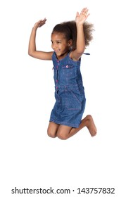 Adorable cute african child with afro hair wearing a denim dress. The girl is jumping and smiling.