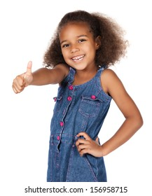 Adorable cute african child with afro hair wearing a denim dress. The girl is showing a thumbs up to the camera.