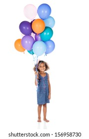 Adorable cute african child with afro hair wearing a denim dress. The girl is holding a bunch of bright coloured helium balloons.