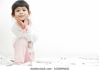 Adorable cute asian little girl on her bed. Waking up making expression. Stay Positive Concept