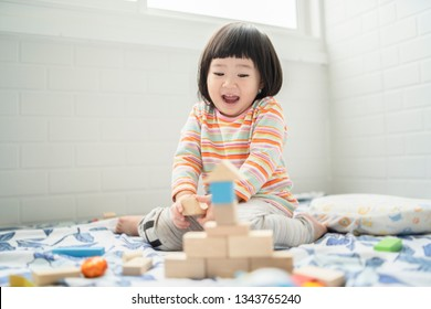 Adorable cute beautiful little Asian baby girl playing with educational wooden toys Healthy happy toddler  colorful wood block indoors at home or nursery, child learning color and forms family concep