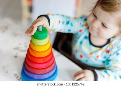 Adorable cute beautiful little baby girl playing with educational toys at home or nursery. Happy healthy child having fun with colorful wooden rainboy toy pyramid. Closeup of hands