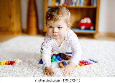 Adorable cute beautiful little baby girl playing with educational toys at home or nursery. Happy healthy child having fun with colorful music toy xylophone Kid learning different skills