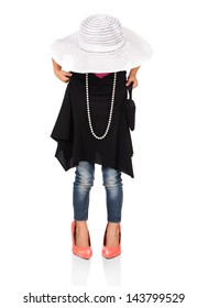 Adorable cute caucasian girl is playing dress up. She is wearing a black dress, white hat, earrings and coral high heel shoes.