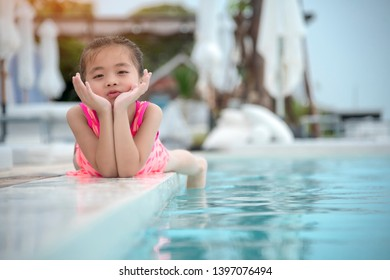 Adorable cute child have fun at swimming pool with smiling face on swimming suit.