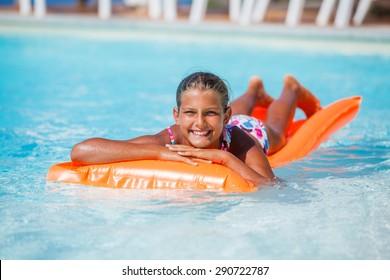 Adorable cute girl relaxing at swimming pool