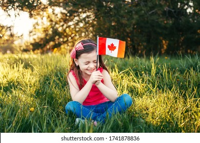 Adorable cute happy Caucasian girl holding Canadian flag. Smiling child sitting on grass in park holding Canada flag. Kid citizen celebrating Canada Day holiday on first day of July outdoor.