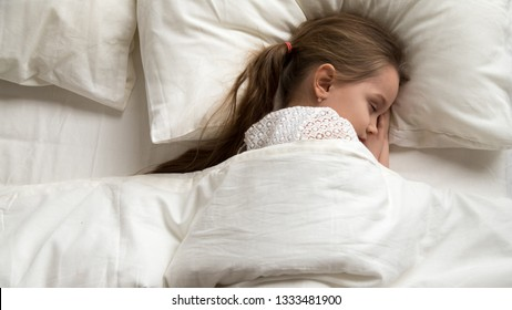 Adorable cute little baby girl sleeping alone in comfortable bed lying on soft pillow covered with warm duvet, calm kid resting asleep in good night healthy peaceful sleep nap in bedroom, top view