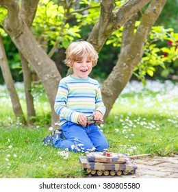 Adorable cute little child playing with toy tank, outdoors. Happy kid boy having fun on sunny summer day. Leisure, lifestyle for kids concept.