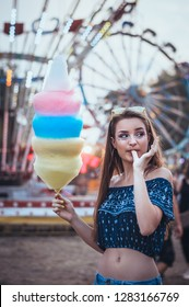 Adorable cute pretty woman with dark hair stands in middle of amusement park, in front of ride with bright colours positive and cheerful, eats pink cotton candy floss, happy and optimistic - Image