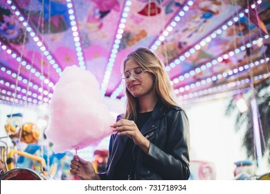 Adorable cute pretty woman stands in middle of amusement park, in front of ride with bright colours positive and cheerful, eats pink cotton candy floss, happy and optimistic