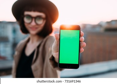 Adorable cute and pretty young woman in hipster millennial trendy outfit shows smartphone with chroma key for own image to camera, smiles on rooftop with amazing sunset
