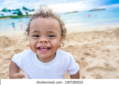 Adorable cute smiling mixed race little boy playing and having fun on a beach vacation. Close up view of his happy expression