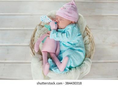 adorable cute sweet baby girl sleeping in white basket on wooden floor hugging tilda rabbits