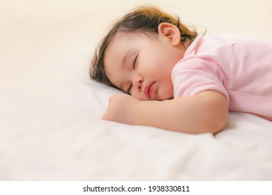 Adorable cute toddler or baby girl sleeping on bed at night with sweet dream in bedroom Lovely child get deep sleep and get relax and happy during lying down on bed Little infant girl get good sleep