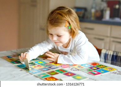 Adorable cute toddler girl playing picture card game at home or nursery. Happy healthy child training memory, thinking. Development step and education of kid.