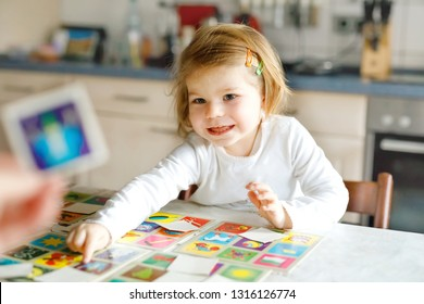 Adorable cute toddler girl playing picture card game with mother or father. Happy healthy child training memory, thinking. Development step and education of kid.