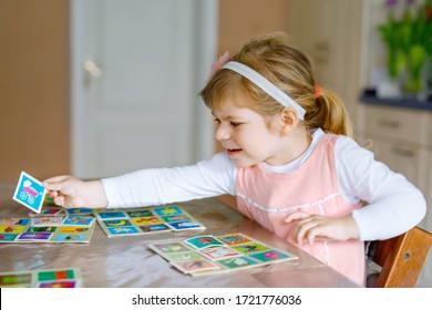 Adorable niñita linda jugando a la carta de fotos. Felices recuerdos de entrenamiento infantil saludable, pensando. Deporte interno creativo y educación de niños durante la pandemia del coronavirus covid enfermedad de cuarentena