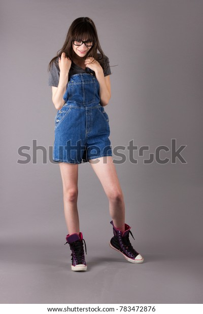 Adorable Cute Young Millennial Woman in Overalls and Cute Shoes