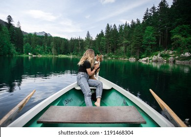 Adorable, cute young woman with blond hair in casual outfit sits together with her best friend, basenji puppy dog and cuddles in rowing boat in lush green forest surroundings of alpine lake