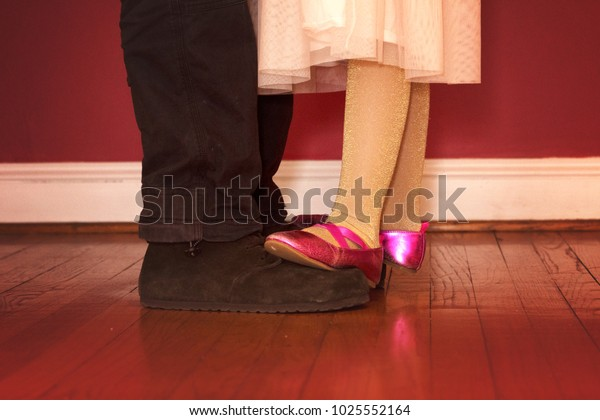 adorable daughter dancing on father's feet