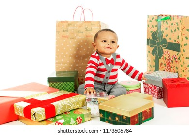 An adorable, dressed up baby boy happily looking up while surrounded by wrapped Christmas gifts.  On a white background.