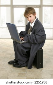 Adorable eight year old boy in father's business suit sitting on briefcase with laptop computer.