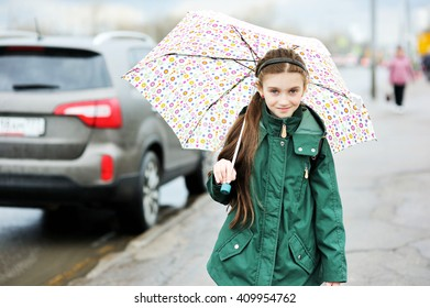 Adorable, elegant school aged kid  girl ,holding colorful umbrella walking in the city street in rainy day