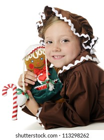 "An adorable elementary ""gingerbread girl"" hugging her gingerbread girl doll.  On a white background."