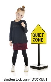 "An adorable elementary ""teacher/librarian"" sternly pointing her finger at the viewer in front of a ""quiet zone"" sign.  On a white background."