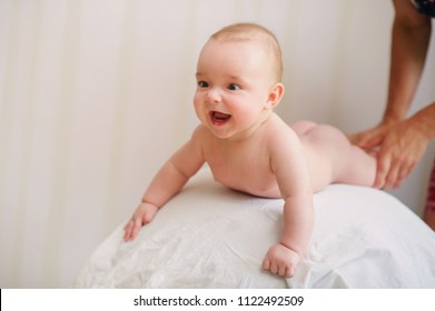 Adorable emotional baby boy standing on arms during massage by therapist. How massaging your baby helps development. Exercises on a ball to strengthen baby body