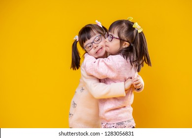 Adorable extraordinary children. Charming positive sisters with chromosome abnormality hugging each other and being extremely lovely
