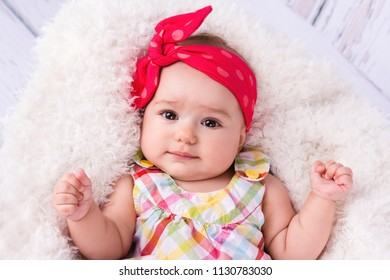 Adorable face of beautiful little baby girl wearing head scarf and looking towards camera