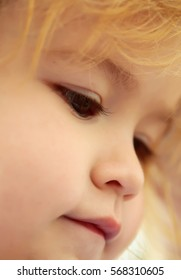 Adorable face of cute baby boy with brown eyes, cheeks and blond hair outdoors on sunny day on blurred background