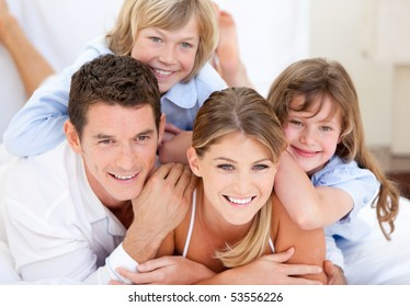 Adorable family looking together at the camera  in the bedroom
