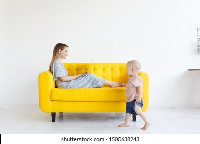 Adorable female freelancer mom in casual dress works remotely on portable laptop computer on yellow sofa, studying forum for mothers, starting business at home while kid is playing alone. Copy space
