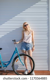 Adorable fitness Hipster female, cycler street rider in stylish sunglasses and trendy summer outwear expressing happiness and satisfaction during photoshoot near her bicycle, isolated on white.