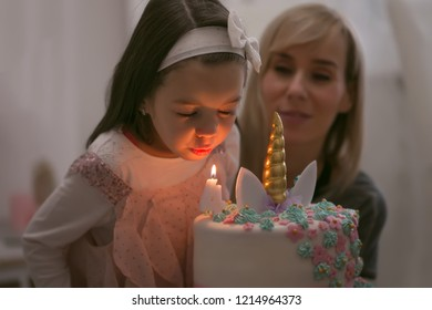 Adorable four year old girl celebrating his birthday and blowing candles on homemade baked cake