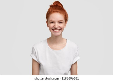 Adorable freckled young lady or teenager smiles joyfully at camera, has red hair combed in knot, dressed at casual t shirt in one tone with background, thinks about good things. Emotions concept