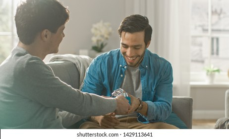 Adorable Gay Boyfriend Gifts a Beautiful Shiny Gift Box to His Cute Hispanic Fiance. Surprised Partner is Extremelly Happy and Hugs His Queer Friend. Relationship Goals.